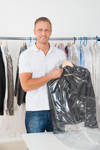 Man Holding Coat In Dry Cleaning Storeの写真素材 [FYI00653388]
