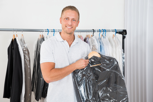 Man Holding Coat In Dry Cleaning Storeの写真素材 [FYI00653389]
