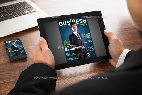 Businessman Reading Online Magazineの写真素材 [FYI00653410]