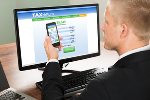 Businessman Looking At Online Tax Return Formの写真素材 [FYI00653435]