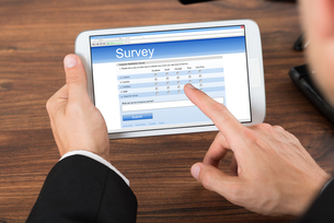 Businessperson With Mobile Phone Showing Survey Formの写真素材 [FYI00653469]