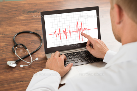 Doctor Looking At Heartbeat Cardiogramの写真素材 [FYI00653476]