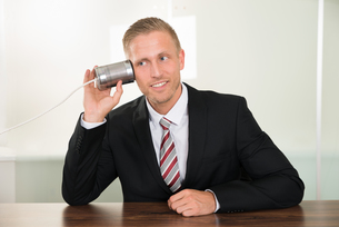 Businessman Listening From Tin Cans Phoneの写真素材 [FYI00653478]
