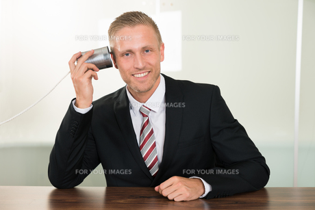 Businessman Listening From Tin Cans Phoneの写真素材 [FYI00653483]