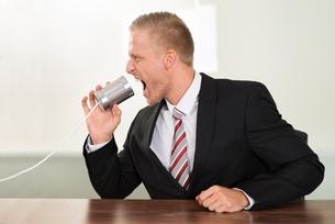 Businessman Screaming In Tin Cans Phoneの写真素材 [FYI00653487]