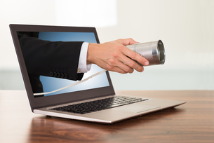 Businessperson Hand With Cans Phone From Laptopの写真素材 [FYI00653488]