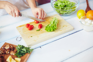 Cutting tomatoes and lettuceの写真素材 [FYI00653601]