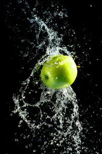Green apple with water splash, on blackの素材 [FYI00653620]