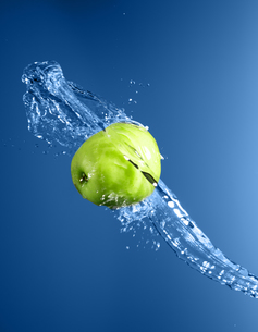 Green apple with water splash, on blue waterの写真素材 [FYI00653621]