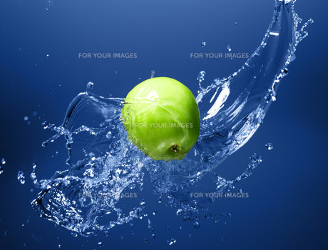 Green apple with water splash, on blue waterの写真素材 [FYI00653623]