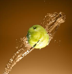 Green apple with water splash, on beigeの写真素材 [FYI00653626]