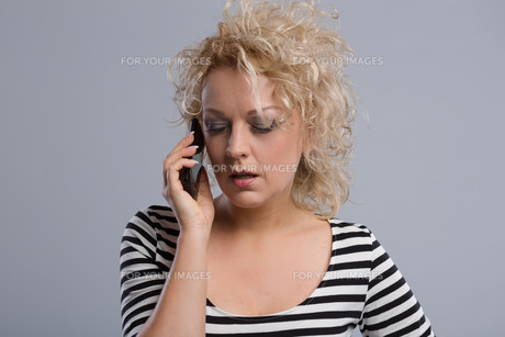 young woman phoning emotionallyの写真素材 [FYI00653656]