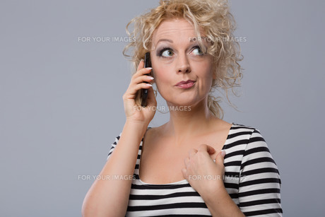 young woman phoning emotionallyの写真素材 [FYI00653657]