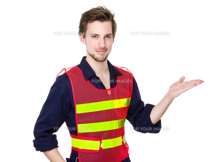 Smiling construction worker presenting productの素材 [FYI00653700]