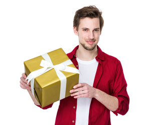 Young handsome man giving present gift boxの写真素材 [FYI00653706]