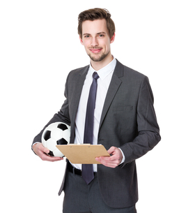 Businessman holding football on whiteの写真素材 [FYI00653781]