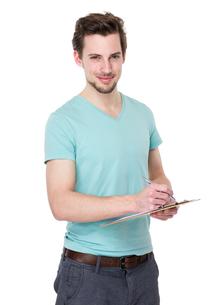 Caucasian man take note on clipboardの写真素材 [FYI00653785]