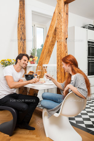 young couple sitting in the morning while having breakfast in the kitchenの写真素材 [FYI00653835]