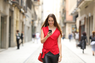 Fashion woman walking and using a smart phoneの写真素材 [FYI00653962]