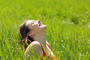 Happy girl face breathing fresh air in a meadowの写真素材 [FYI00653965]