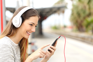Teen girl listening to the music with headphones waiting a trainの写真素材 [FYI00653969]