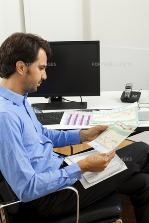 young businessman sitting with documents on a sreibtisch officeの素材 [FYI00654034]