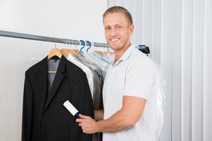 Man With Lint Roller In Clothes Storeの写真素材 [FYI00654075]