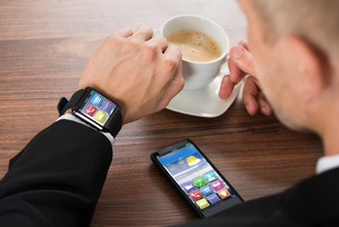 Businessman With Smartphone And Smartwatch Drinking Coffeeの写真素材 [FYI00654076]