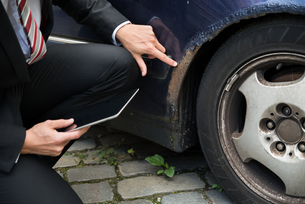 Insurance Agent Examining Car Damagedの写真素材 [FYI00654090]