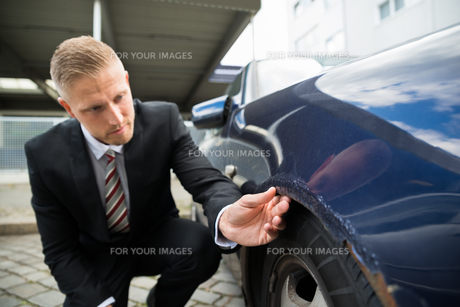 Man Looking For Scratches On His Carの写真素材 [FYI00654094]