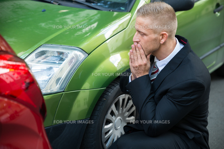 Upset Driver Looking At Car After Traffic Collisionの写真素材 [FYI00654100]