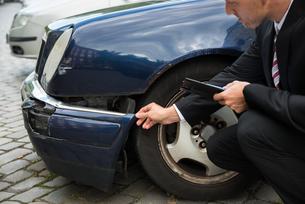 Insurance Expert Examining Car Damageの写真素材 [FYI00654104]
