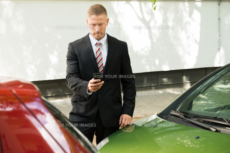 Man Photographing His Vehicle After Traffic Collisionの写真素材 [FYI00654116]