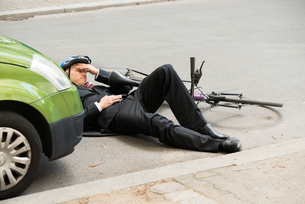 Male Cyclist After Car Accident On Roadの写真素材 [FYI00654127]