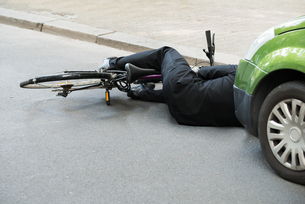 Male Cyclist After Car Accident On Roadの写真素材 [FYI00654129]