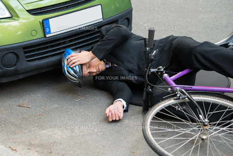 Male Cyclist After Car Accident On Roadの写真素材 [FYI00654130]