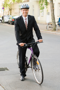 Happy Man In Suit Riding Bicycleの写真素材 [FYI00654134]