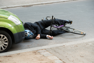 Male Cyclist After Car Accident On Roadの写真素材 [FYI00654135]