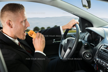 Businessman Eating Snack While Drivingの写真素材 [FYI00654176]