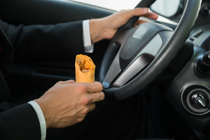 Close-up Of A Male Holding Snack While Drivingの写真素材 [FYI00654179]