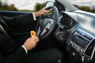 Close-up Of A Male Holding Snack While Drivingの写真素材 [FYI00654180]