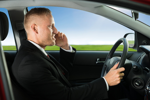 Man Using Cellphone While Drivingの写真素材 [FYI00654182]