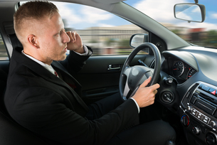 Man Using Cellphone While Drivingの写真素材 [FYI00654183]