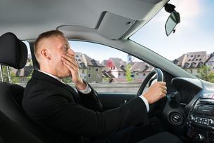 Businessman Yawning While Driving Carの写真素材 [FYI00654184]