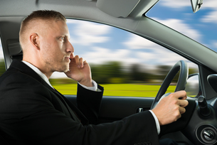 Man Using Cellphone While Drivingの写真素材 [FYI00654185]