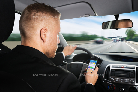 Businessman Using Cellphone While Driving A Carの写真素材 [FYI00654205]