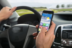 Person's Hand Using Cellphone While Driving A Carの写真素材 [FYI00654206]
