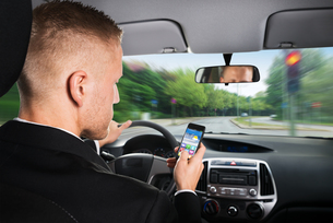 Businessman Using Cellphone While Driving A Carの写真素材 [FYI00654208]