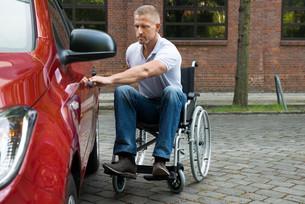 Handicapped Man Opening Door Of A Carの写真素材 [FYI00654243]