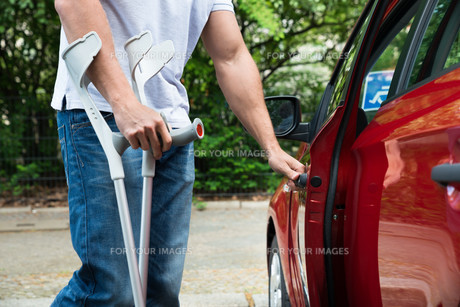 Disabled Man Opening Door Of A Carの写真素材 [FYI00654248]